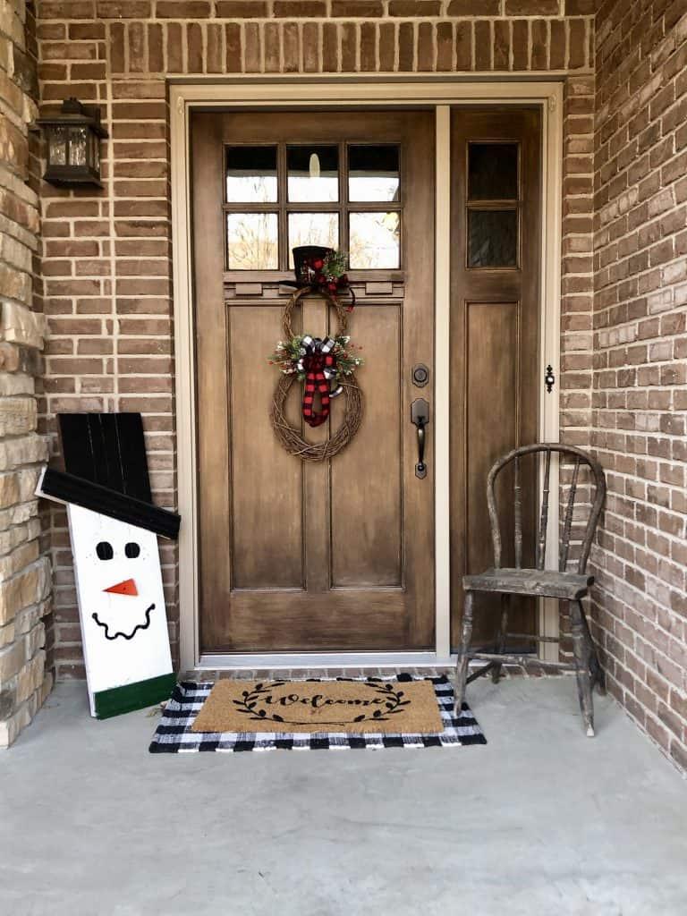 Dark colored Winter wreath on dark wooden door