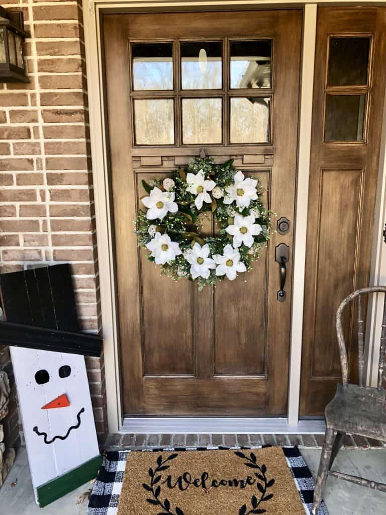 White Winter wreath on dark wooden door
